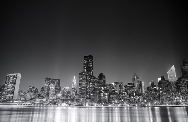New York City - Night  - By Vivienne Gucwa  I have been traipsing all over the city for the last few months trying to capture a large majority of New York City's skyline views. I think everyone has a particular skyline view they immediately think of when they think of the city. And yet, it's still incredible to me after all this time that I come across different skyline angles that I hadn't previously come across or had the time to explore before from certain vantage points.  New York City has several prominent skyline views that are popular. One is in lower Manhattan and usually includes the skyscrapers of the Financial District along with the one or more of the bridges that serve the lower part of Manhattan. The other series of skyline views can be found from the top of a few popular skyscrapers in midtown Manhattan. Another series of skyline views involves the midtown Manhattan skyline as seen from different vantage points across (or in some cases directly from) the East River. This particular view is taken from one of the latter vantage points. It's a 30 second long exposure taken on a gorgeously clear and cold night in the beginning of March from Roosevelt Island.  Prominent skyscrapers in this view are the Chrysler Building and the United Nations building (all the way to the left). The lights of other famous midtown skyscrapers can also be seen even if those skyscrapers (looking at you Empire State Building) are hidden in this view. The lights directly in front of the skyscrapers that line the East River belong to the FDR Drive, a major traffic route that lines New York City's east side.  --------